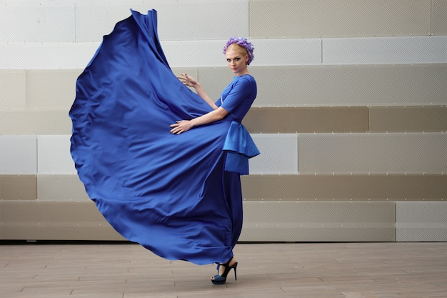 Volledig lengteportret van een maniervrouw met haar kleding die in de lucht vliegt Premium Foto