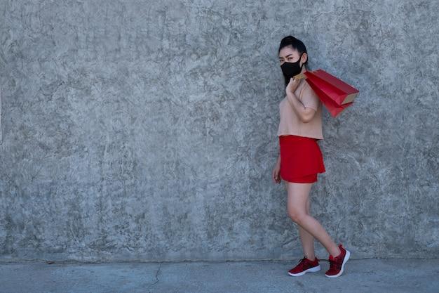 Volledig lengteportret van een mooie jonge aziatische vrouw die een gezichtsmasker draagt met boodschappentassen op betonnen muur, vrouwen dragen roze kleding en rode rok kijken naar de camera Premium Foto