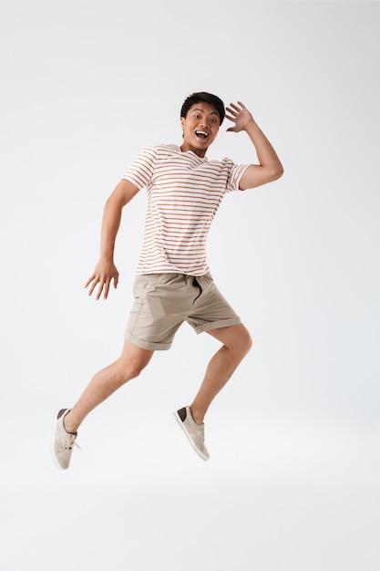 Volledig lengteportret van een opgewonden jonge aziatische mens Premium Foto