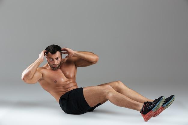 Volledig lengteportret van een spier sterke shirtless mannelijke bodybuilder Gratis Foto