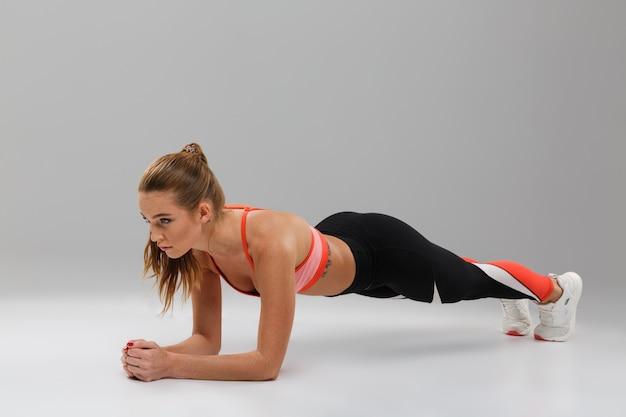 Volledig lengteportret van een vrij geschikte sportvrouw die plank doet Gratis Foto