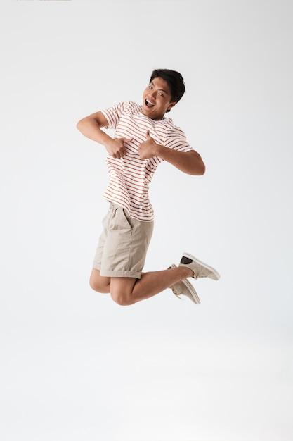 Volledig lengteportret van een vrolijke jonge aziatische mens Premium Foto