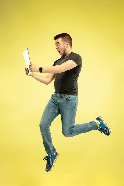 Volledig lengteportret van gelukkige springende mens met gadgets die op geel worden geïsoleerd. Gratis Foto