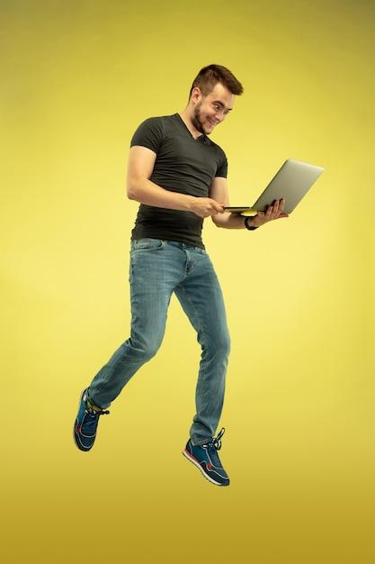 Volledig lengteportret van gelukkige springende mens met gadgets die op geel worden geïsoleerd Gratis Foto