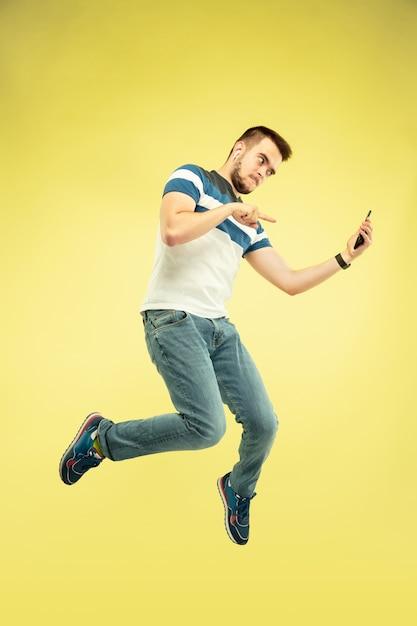 Volledig lengteportret van gelukkige springende mens met gadgets op geel Gratis Foto