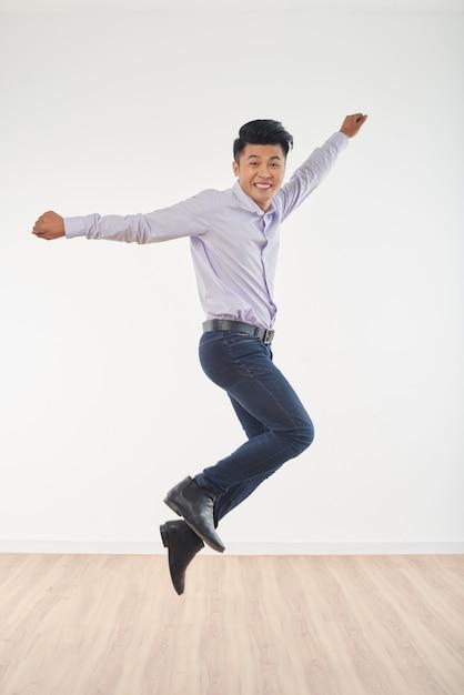 Volledig lengteportret van jonge mens die volledig van geluk springt Gratis Foto
