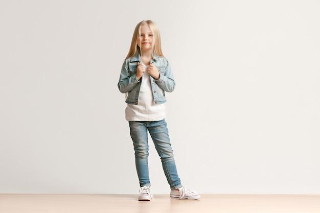 Volledig lengteportret van leuk klein jong geitjemeisje in modieuze jeanskleren die camera bekijken en glimlachen, die zich tegen witte studiomuur bevinden. kindermode concept Gratis Foto