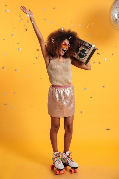 Volledig lengteportret van mooie dolblije vrouw van de afro amerikaanse disco met opgeheven hand, die zich op rolschaatsen bevinden, die boombox houden Gratis Foto