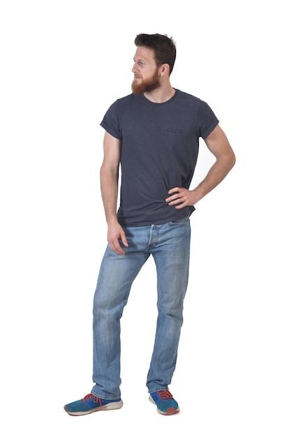 Volledig portret van een man met zijn hand op zijn taille en kijkend naar de zijkant op wit Premium Foto