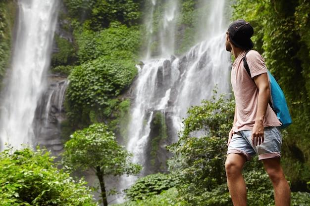 Volledig portret van jonge wandelaar of avonturier in spijkerbroek en snapback die van de natuur geniet Gratis Foto