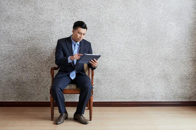 Volledig schot van aziatische zakenman die tabletpc met behulp van gezet in leunstoel in een lege ruimte Gratis Foto