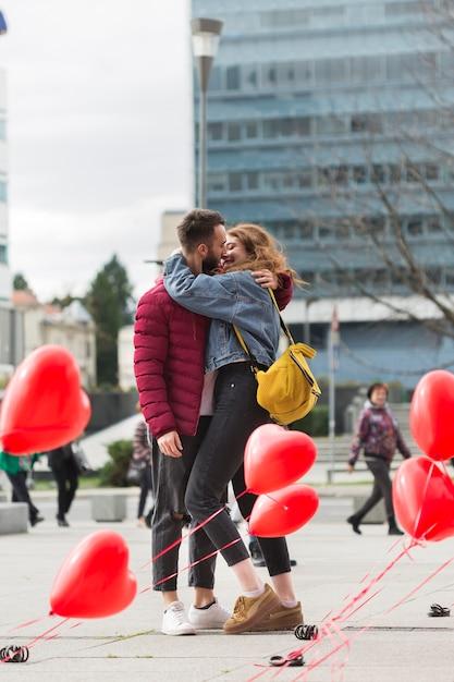 Volledig schot van het mooie paar kussen Gratis Foto