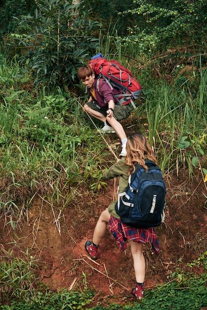 Volledig schot van mannelijke wandelaar die een helpende hand uitbreiden tot een vrouwelijke wandelaar die een heuvel proberen op te zetten Gratis Foto