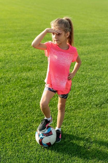 Volledig schot van meisje met roze t-shirt en bal Gratis Foto