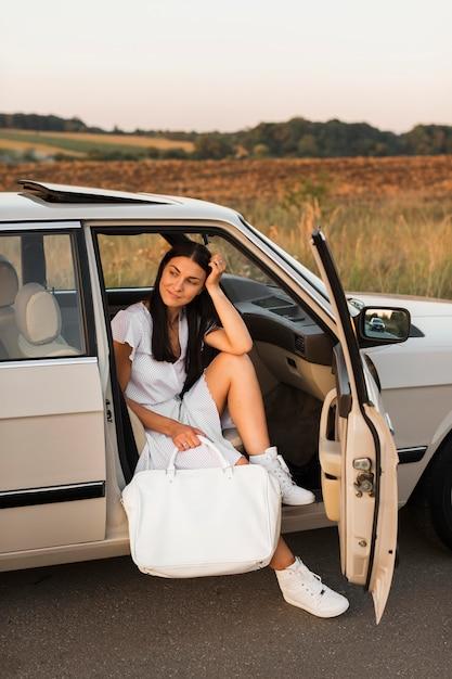 Volledig schot vrouw poseren in auto Gratis Foto