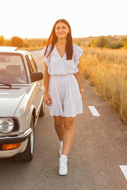 Volledig schot vrouw poseren in de buurt van auto Gratis Foto