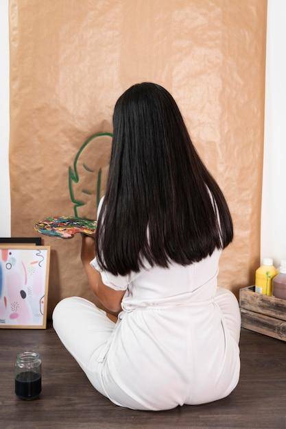 Volledig schot vrouw schilderij blad Gratis Foto