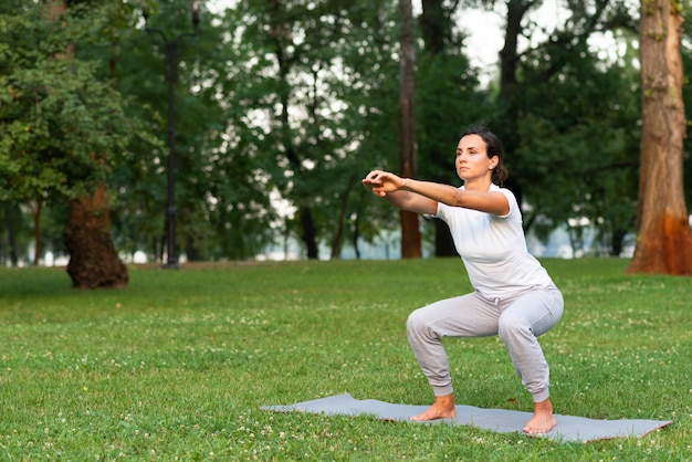 Volledige geschotene vrouw die hurkzit op yogamat doet Gratis Foto