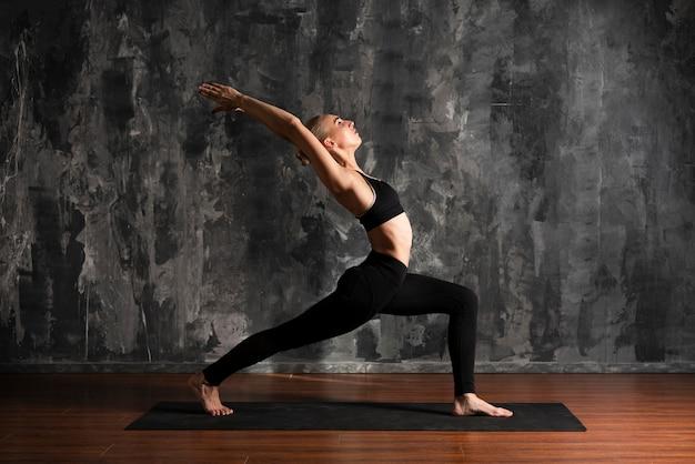 Volledige geschotene vrouw die yoga op mat doet Gratis Foto