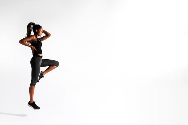 Volledige geschotene vrouw die zich op één been bevindt Gratis Foto