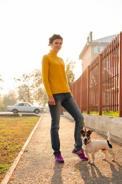 Volledige geschotene vrouw met haar hond in openlucht Gratis Foto