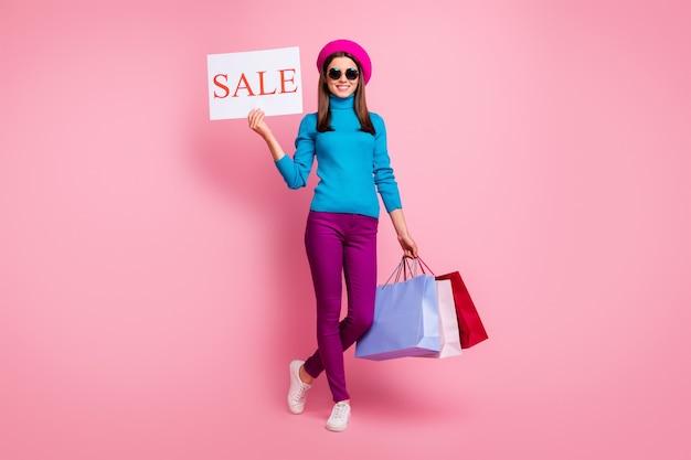 Volledige lengte lichaamsgrootte weergave van haar ze mooi aantrekkelijk modieus vrolijk vrolijk meisje in handen houden tassen promo advertentie bord winkel openen. Premium Foto