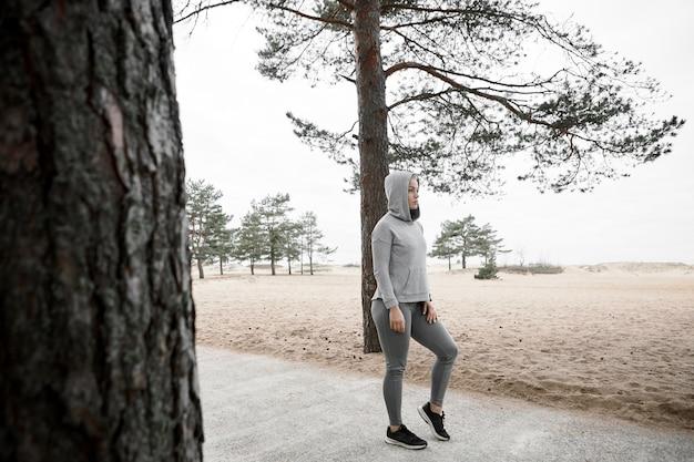 Volledige lengte shot van coole modieuze europese vrouwelijke atleet warming-up lichaam voor cardiotraining buitenshuis, stijlvolle sneakers, legging en hoodie dragen, staande op verharde pad in bos of park Gratis Foto