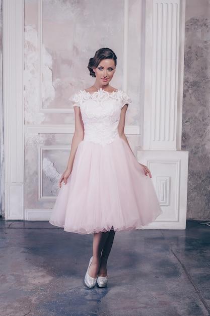 Volledige lengte shot van prachtige slanke vrouw met lang golvend haar poseren in casual witte jurk en zwarte hoge hakken met arm op heup Premium Foto