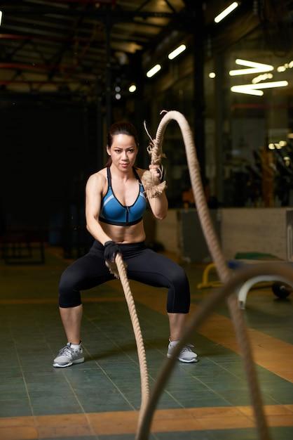 Volledige lengte van fit meisje doet crossfit oefening Gratis Foto