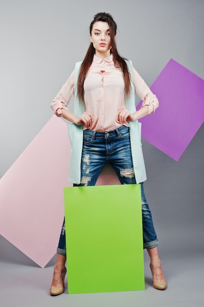 Volledige lengte van mooi meisje, met groen leeg reclamebord, over grijze achtergrond en roze en violette banner Premium Foto