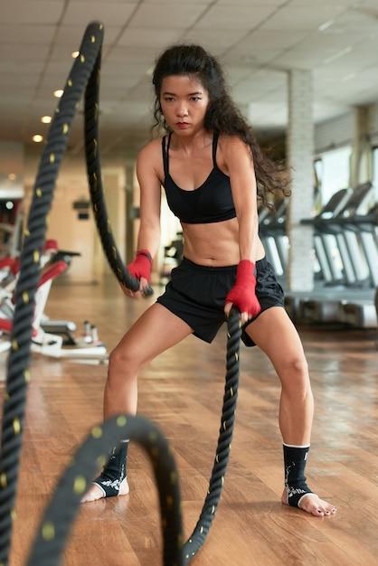 Volledige lengte van sportvrouw die strijdtouwoefening uitvoert Gratis Foto