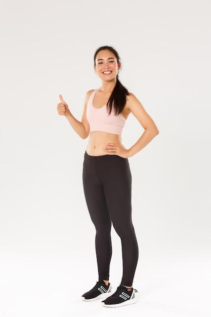 Volledige lengte van tevreden lachend, schattig aziatisch fitness meisje, sportvrouw in actieve slijtage met thumbs-up en glimlachend tevreden, trotse vrouwelijke athelte krijgt dagelijks trainingsdoel, witte achtergrond. Gratis Foto