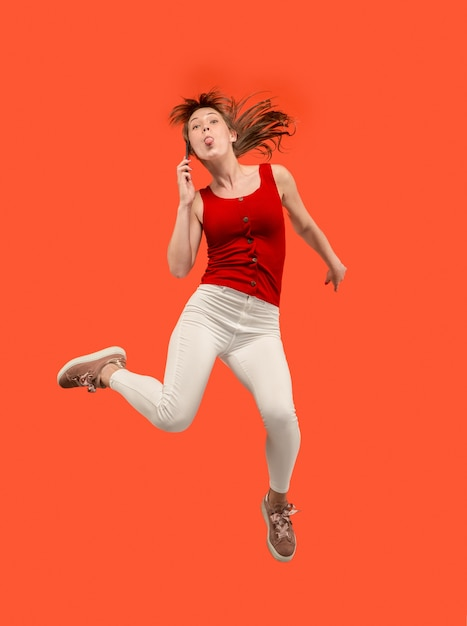 Volledige lengte van vrij jonge vrouw die telefoon neemt terwijl het springen tegen rode studioachtergrond. Gratis Foto