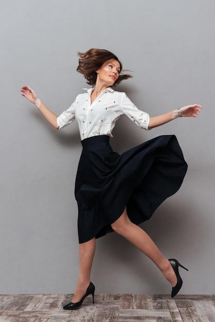 Volledige lengte van vrouw in bedrijfskleren die in studio lopen en terug op grijs kijken Gratis Foto