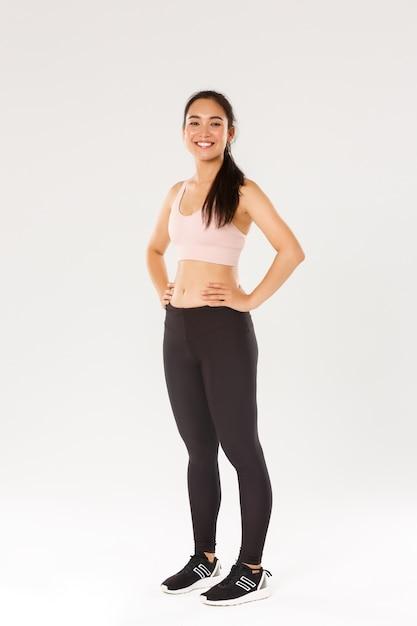 Volledige lengte van zweterig lachend fitnessmeisje, vrouwelijke athelte in actieve slijtage kijkt tevreden tijdens het trainen, training in de sportschool, tevreden met oefeningen, coach helpt perfect lichaam te krijgen, witte muur Premium Foto