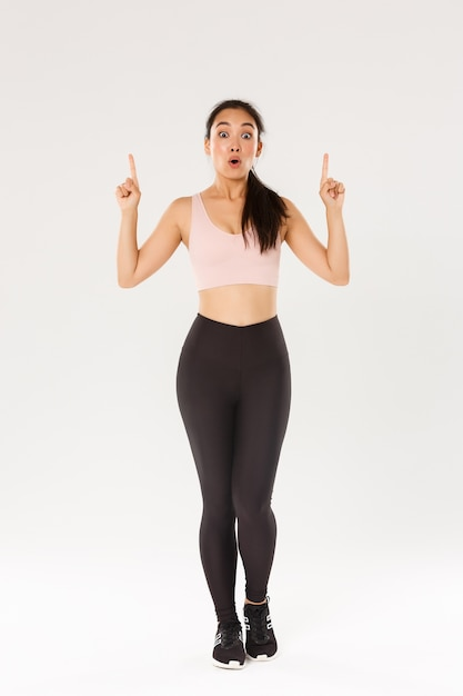 Volledige lengte verbaasd en onder de indruk van vrouwelijke aziatische atleet, sportvrouw in sportkleding zegt wauw en wijst met de vingers omhoog. Premium Foto