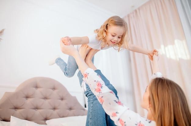 Volledige lengte zijaanzicht gelukkige jonge moeder liggend op bed, tillen peuter kind dochter. klein jong geitjemeisje die vliegtuig maken, die pret met sterke mama samen in slaapkamer hebben Premium Foto