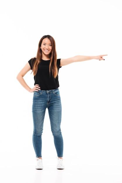 Volledige lengtefoto van gelukkige charmante aziatische vrouw in vrijetijdskleding die zich met uitgestrekte hand bevindt, wijzend met vinger, bekijkend camera Gratis Foto