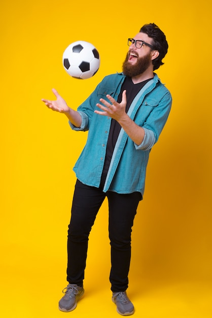 Volledige lengtefoto van verbaasde jonge mens met het voetbalbal van de baardholding over geel Premium Foto