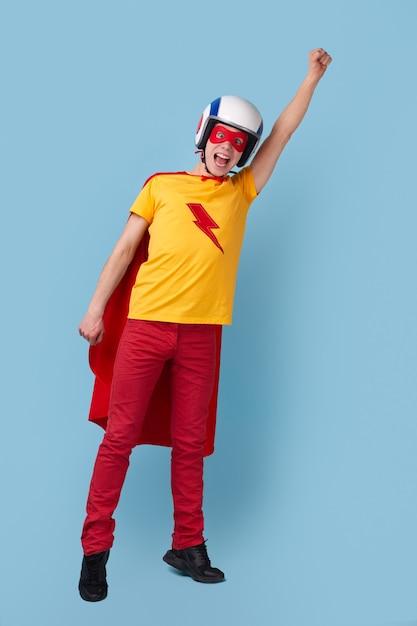 Volledige lichaam opgewonden jonge kerel in superheld cape en helm arm opheffen en schreeuwen terwijl ze doen alsof ze vliegen tegen blauwe achtergrond Premium Foto