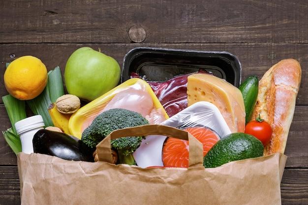 Volledige papieren zak verschillende gezonde voeding op witte houten tafel. fruit, groenten, vis en vlees Premium Foto