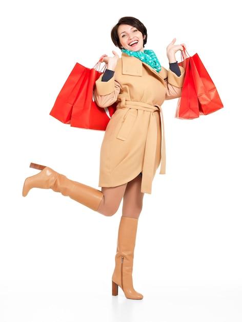 Volledige portret van gelukkige vrouw met boodschappentassen in herfst jas met groene sjaal staande geïsoleerd op wit Gratis Foto