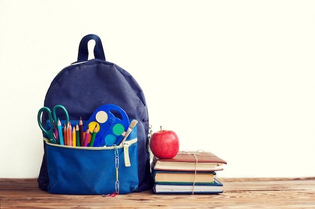 Volledige schoolrugzak met boeken en appel op wit. Premium Foto