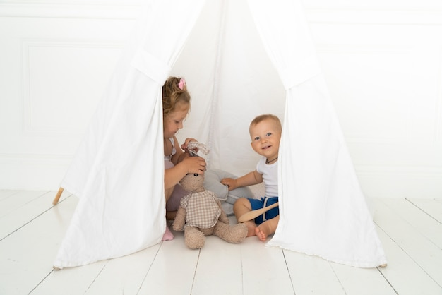 Volledige shot gelukkige kinderen onder de tent Gratis Foto