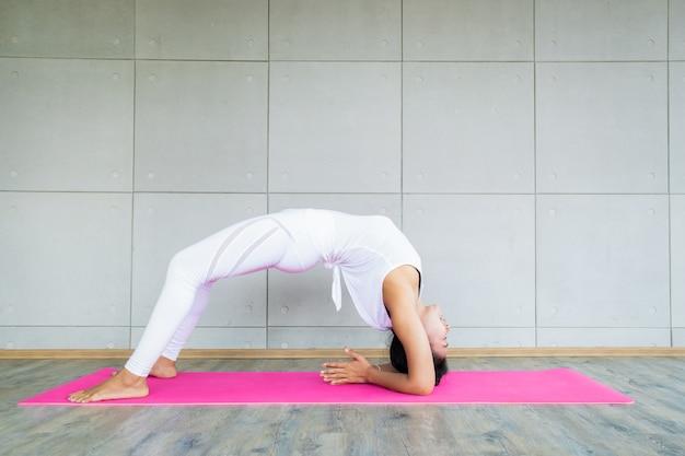 Volwassen aziatische vrouw die een yogaoefening in de oefeningsruimte doet in haar huis. Premium Foto