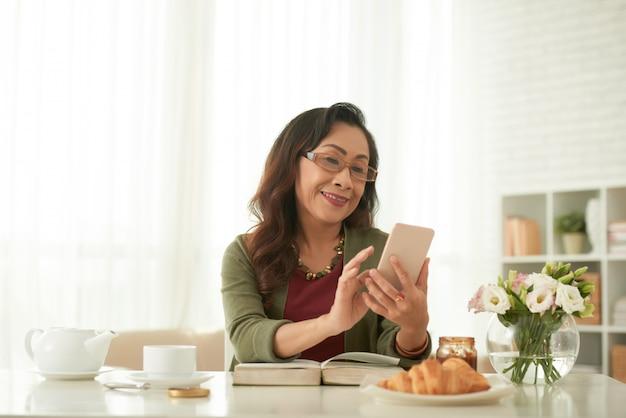 Volwassen aziatische vrouw die internet surft die haar smartphone-zitting thuis gebruiken bij lijst Gratis Foto