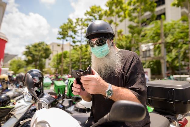 Volwassen bebaarde hipster man met zonnebril en masker met behulp van telefoon zittend op de motorfiets Premium Foto
