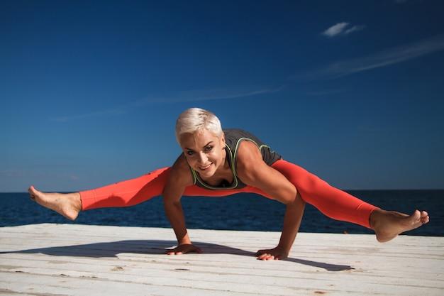 Volwassen blonde vrouw met kort kapsel praktijken yoga op de pier Premium Foto