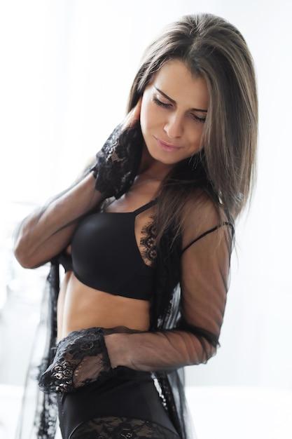 Volwassen brunette vrouw in sexy zwarte lingerie Gratis Foto