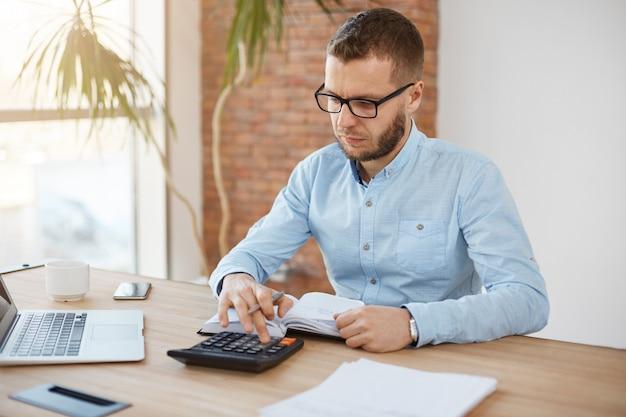 Volwassen ernstige gebaarde kaukasische financiënmanager in glazen en blauw overhemd die in licht comfortabel bedrijfbureau zitten Gratis Foto